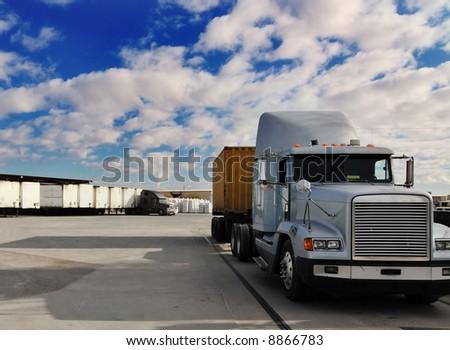 Heavy goods truck leaving loading bay - stock photo