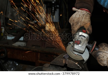 Heavy industry worker cutting steel with angle grinder - stock photo
