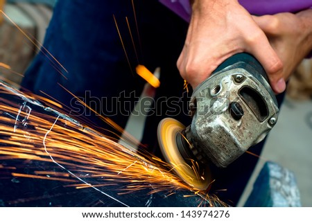 Heavy industry worker cutting steel with angle grinder at car service - stock photo