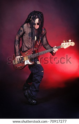 Heavy metal musician  is playing electrical guitar. Shot in a studio. - stock photo