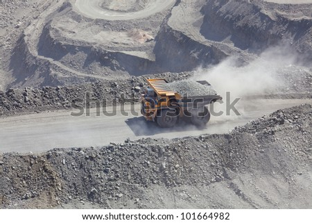 Heavy mining dump truck driving along the opencast - stock photo