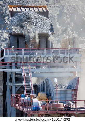 Heavy mining dump truck unloading ore into hopper crusher - stock photo