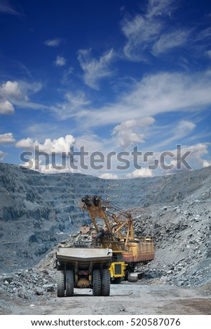 Heavy mining dump trucks are being loaded with iron ore on the opencast mining on a sunny day