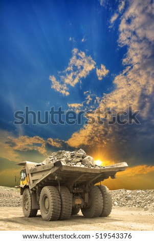 Heavy mining truck loaded with iron ore driving along the opencast on sunset