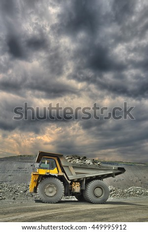 Heavy mining truck loaded with iron ore on the opencast with dramatic sky on the background