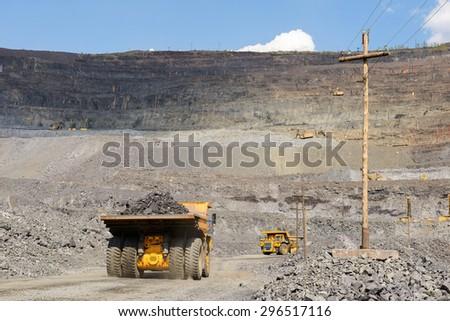 Heavy mining truck on the iron ore opencast mining quarry - stock photo