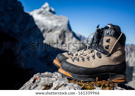 Heavy mountain boots in the mountain environment - stock photo