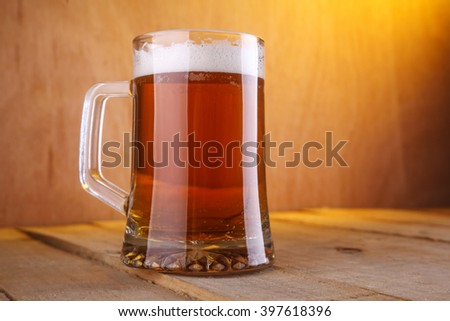 Heavy mug with light beer on a grunge wood surface