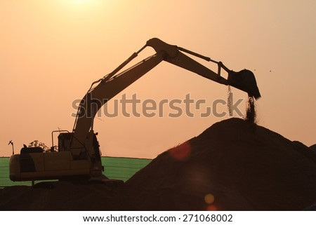 heavy orange excavator with shovel standing on hill with sand