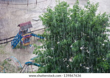Heavy rain against the tree and a children's playground - stock photo