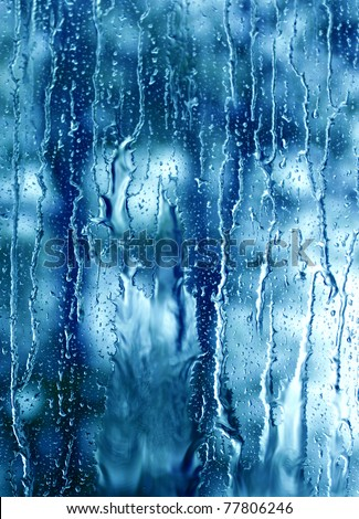 heavy rain drops on blue window - stock photo