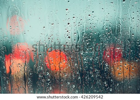 Heavy rain. Raindrop on the window of the car. Abstract blur bokeh of traffic and car light. - stock photo
