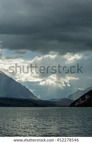 Heavy rain shower passing through the far side of Brienzersee Lake at Switzerland on early summer - stock photo