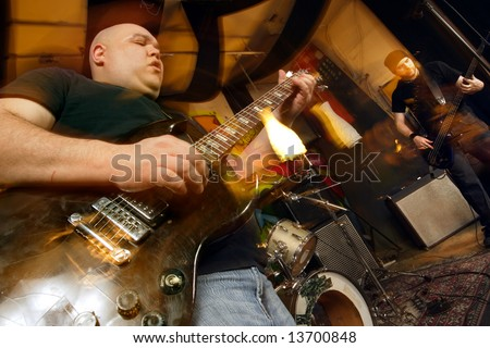 Heavy rock band playing. Shot with strobes and slow shutter speed to create lighting atmosphere and blur effects. - stock photo