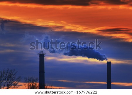 Heavy smoke spewed from coal powered plant smoke stacks under dramatic sunset