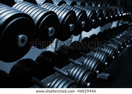 Heavy sports dumbbells in modern sports club - stock photo