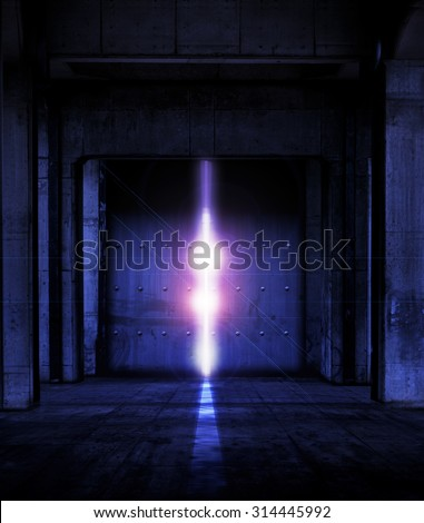 Heavy steel doors opening. Large steel doors at the end of a dark corridor, opening and light coming in. - stock photo