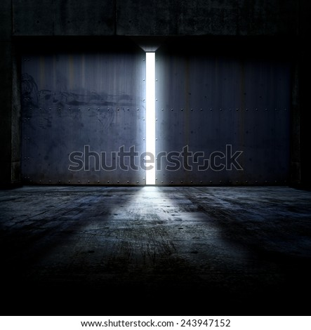 Heavy steel doors opening. Large steel doors of an hanger like building opening and light coming in. - stock photo