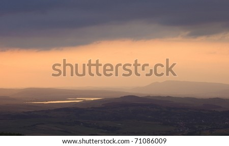 heavy storm clouds gathering over the hill near a lake at sunset - stock photo