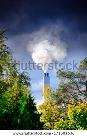 Heavy sunlit smoke and chimney - stock photo
