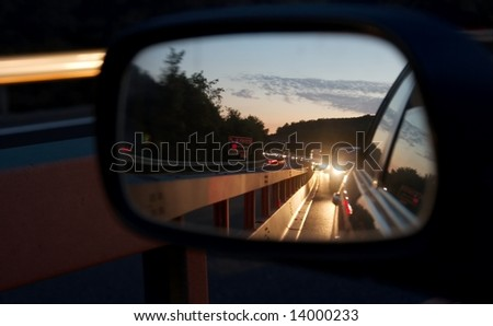 Heavy traffic reflecting in the mirror by night - stock photo