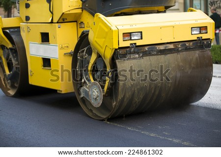 Heavy Vibration roller compactor at asphalt pavement works for road repairing - stock photo
