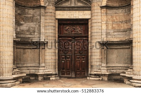 Heavy wooden double door outside of the Saint Nizier church in Lyon, France. Circle wall with square stones and pillars. Latin inscriptions on the sides and the arch. Religious symbolic relief on top.