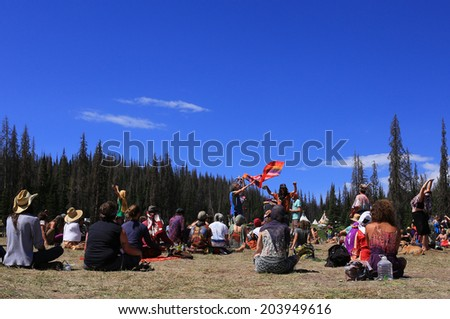 Heber City, Utah, USA. 7/4/14 A crowd meditates at the rainbow gathering in the local forest.