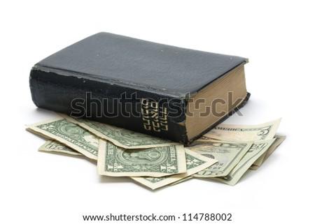 Hebrew bible book on top of dollar bills - stock photo