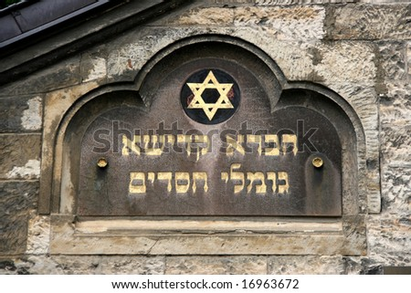 Hebrew writing and Jewish symbol - Star of David, next to old Jewish cemetery and synagogue in Prague, Czech Republic. - stock photo