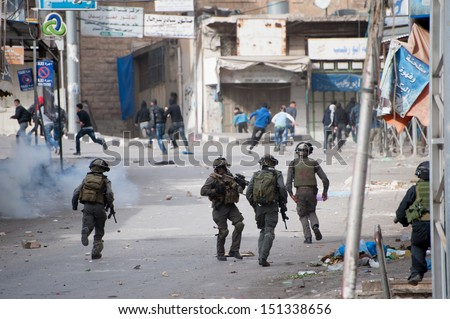 HEBRON, PALESTINIAN TERRITORY - FEBRUARY 22: Israeli forces chase Palestinians in clashes after a protest against the Israeli occupation in the West Bank city of Hebron, February 22, 2013. - stock photo