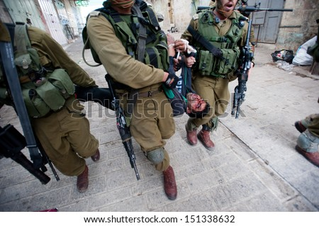 HEBRON, PALESTINIAN TERRITORY - MARCH 1: Israeli soldiers arrest a Palestinian youth, who shows signs of being beaten, following a demonstration in the West Bank city of Hebron, March 1, 2013. - stock photo