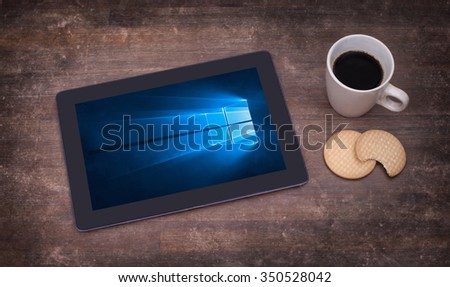 HEERENVEEN, NETHERLANDS, June 6, 2015: Tablet computer with Windows 10 background. Windows 10 is the new version of Windows OS by Microsoft Corporation; it starting July 29, 2015. - stock photo
