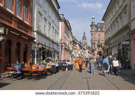 Heidelberg, Germany - April 30, 2014: People sit at an outdoor cafe and walk in the Heidelberg Hauptstrasse main street among shops in the historic center of Heidelberg, Germany on April 30, 2014 - stock photo