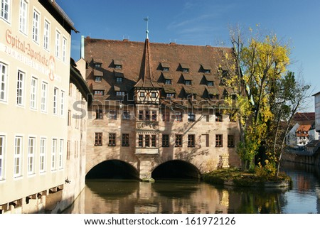 Heilig-Geist-Spital - ancient franconian building overlooking river Pegnitz in Nuremberg - stock photo