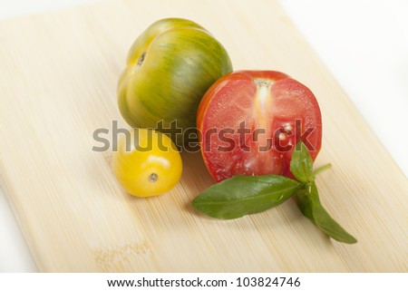 Heirloom tomatoes and basil on a cutting board. - stock photo