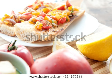 heirloom tomatoes in a salsa on french baguette for a classic bruschetta with basil and olive oil - stock photo