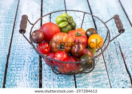 Heirloom tomatoes in basket - stock photo