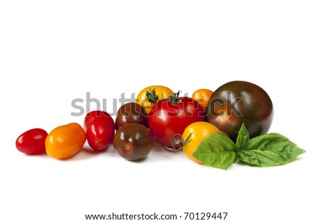Heirloom tomatoes with fresh basil, isolated on white.