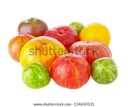 Heirloom tomatoes with water drops on white background