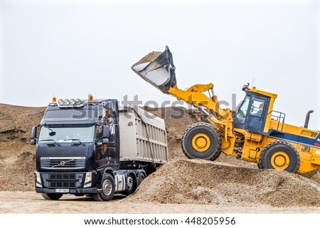 HEKLA,ICELAND-June 25:Bulldozer in action pour white stone in the truck dumper on June 25, 2016 in Hekla, Iceland.