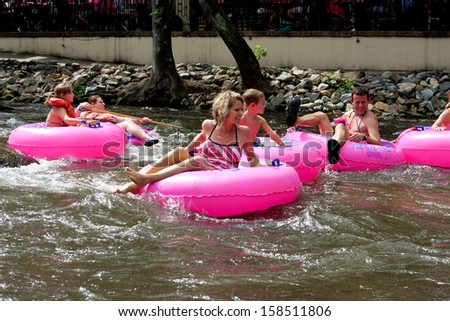 HELEN, GA - AUGUST 24:  A family enjoys tubing down the Chattahoochee River in North Georgia on a warm summer afternoon, on August 24, 2013 in Helen, GA.   Hundreds went tubing down the river.  - stock photo