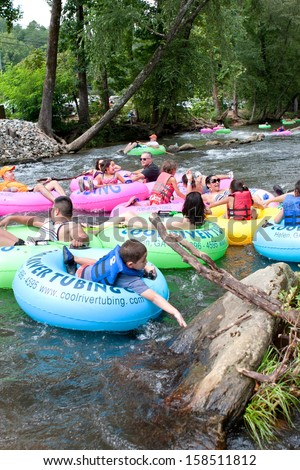 HELEN, GA - AUGUST 24:  Families enjoy tubing down the Chattahoochee River in North Georgia on a warm summer afternoon, on August 24, 2013 in Helen, GA.   Hundreds could be seen  tubing on the river.  - stock photo