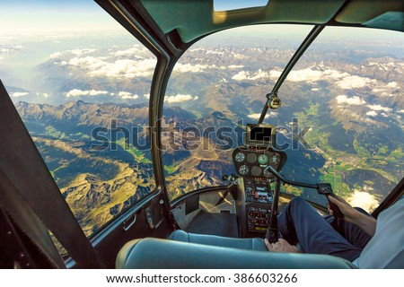 Helicopter cockpit flying on mountain landscape and cloudy sky, with pilot arm driving in cabin. Spectacular aerial view of Alps mountain chain. - stock photo