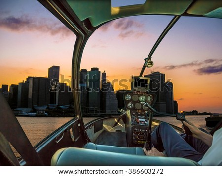 Helicopter cockpit on New York skyline at sunset, with pilot arm and control board inside the cabin - stock photo