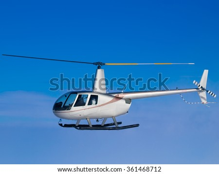 Helicopter flying in blue sky side view - stock photo