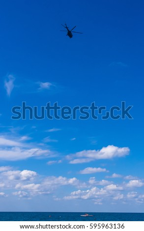 helicopter flying in the blue sky with white clouds over the sea