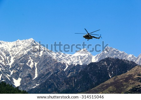 Helicopter flying over snowy mountains