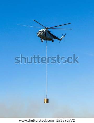 Helicopter in action carrying water bucket over fire.  - stock photo