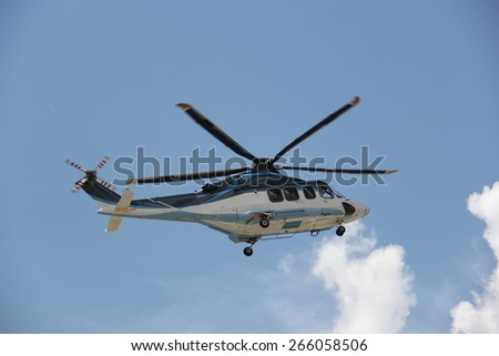 Helicopter is flying in bright blue sky.